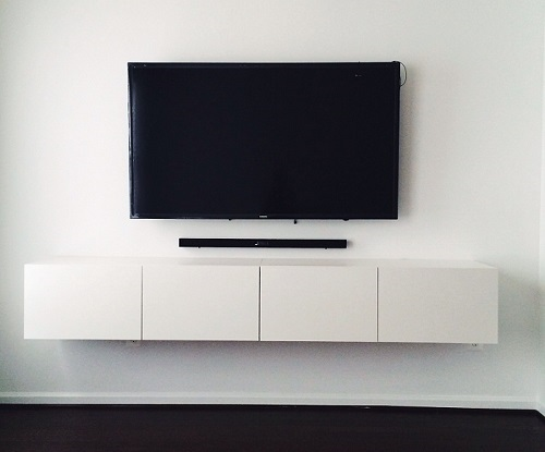 tv mounted on wall with no wires showing